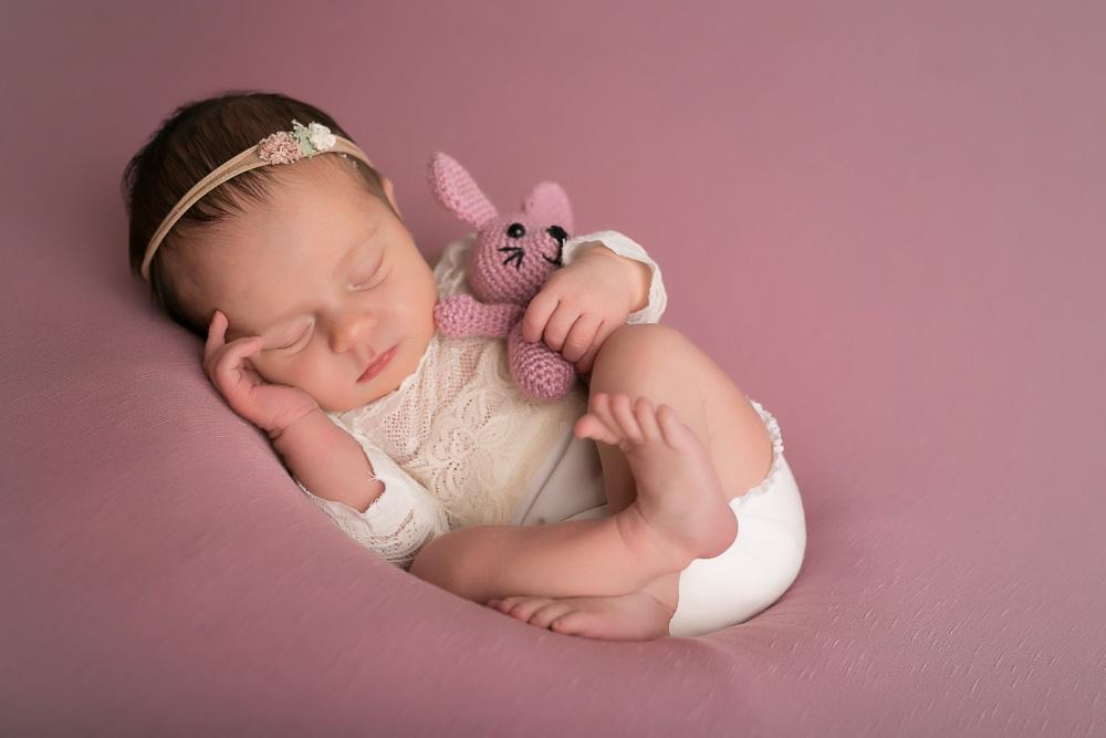 Kleines süßes Baby mit rosa Hasen im Arm.