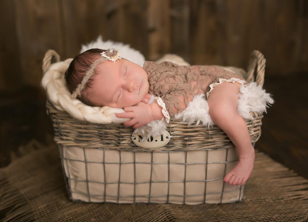 Babyshooting mit einem Baby im Körbchen.