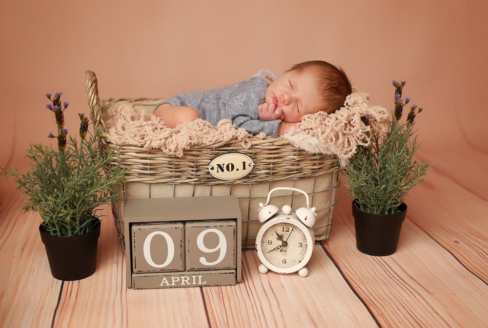 Neugeborenens liegt im Körbchen mit mediterraner Dekoration.