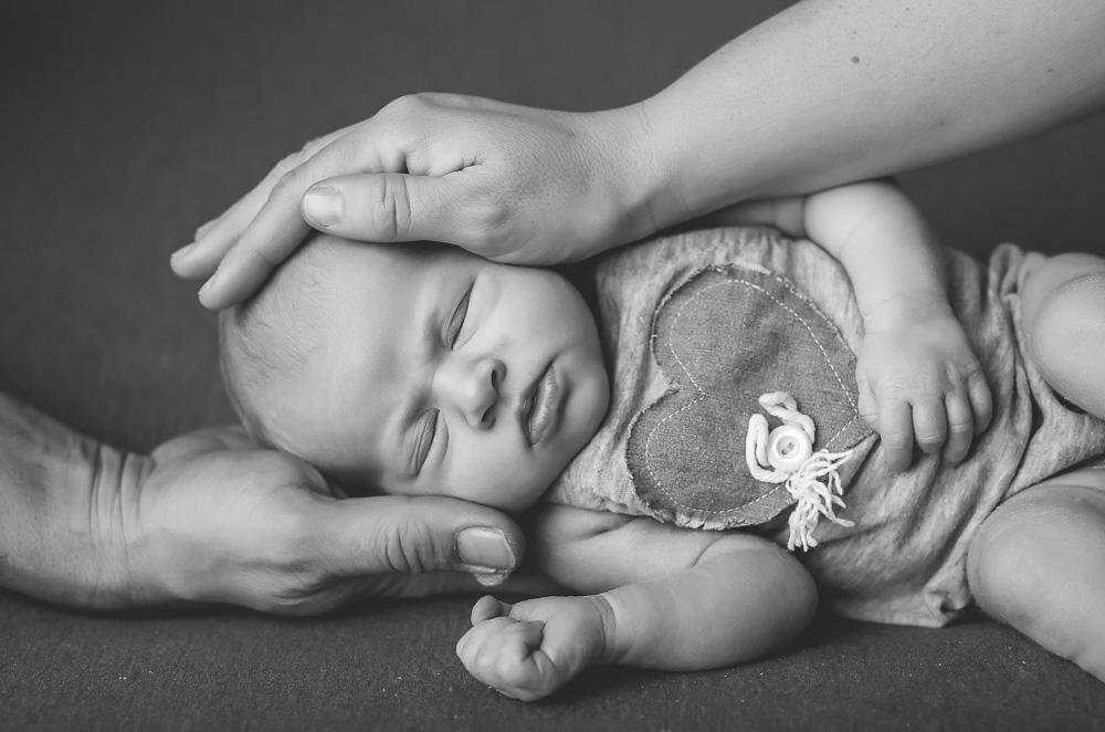 Mama und Papa legen die Hände auf den Kopf des Babys.