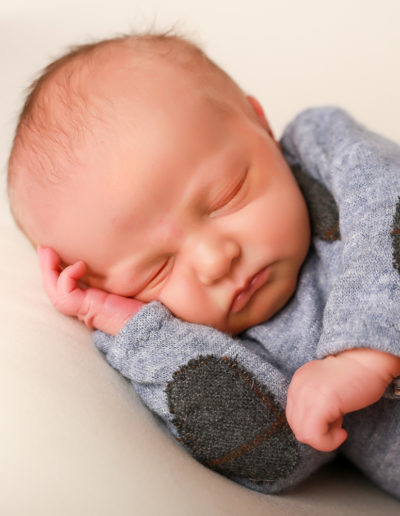 Baby liegt auf der Seite mit süßen Body.