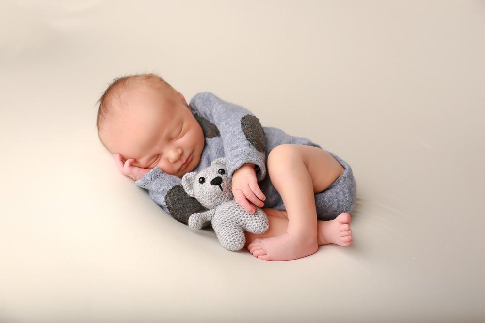 Babyshooting mit kleinem Strampler und Teddy.