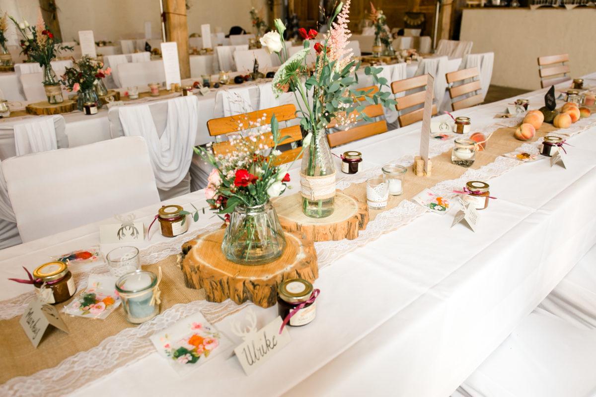 Auf dem Bild sieht man die Tischdekoration mit Holzscheiben, wilden Blumen und Kerzen.