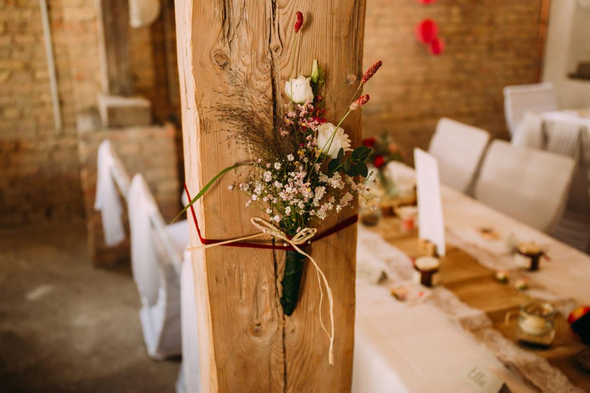 Hochzeitsdeko - Blumenschmuck am Holzbalken.