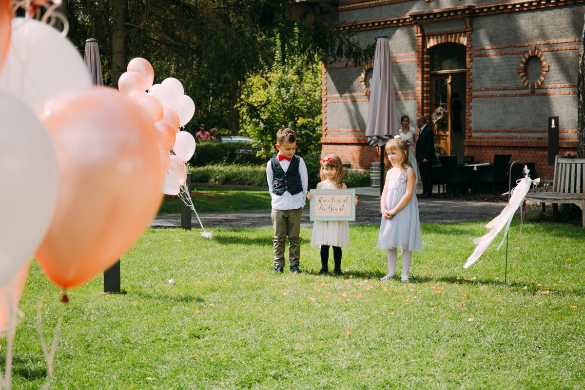 Die Kinder des Brautpaares tragen Schild mit Eheschließung.