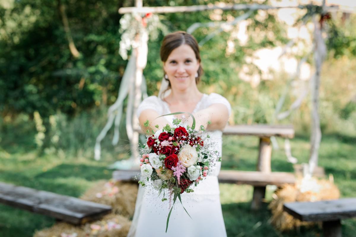 Die Braut hält ihren Brautstrauß in die Kamera zum Brautpaarshooting.