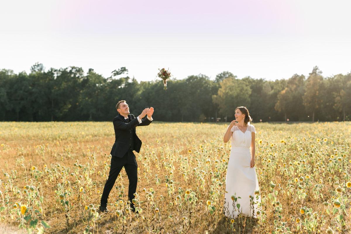 Braut wirft den Brautstrauß zu ihrem Mann (Brautpaarshooting).
